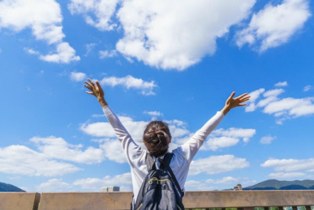 空に向かって手を挙げる女性